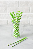 Glass jug with striped green drinking straws brick wall backgrou