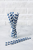 Glass jug with striped blue drinking straws brick wall backgroun