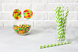 Glass with striped green drinking straws brick wall background