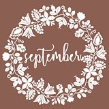 Hand drawn vector september sign with wreath on brown background