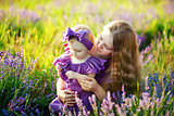 Mother hugs her little daughter in the rays of the setting sun, wearing long lilac dresses
