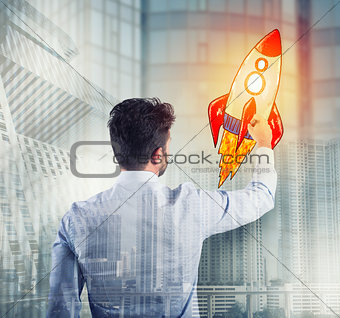 Businessman drawing a rocket. Concept of business improvement and enterprise startup