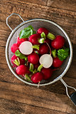 Several red radishes in a sieve