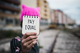 woman with a pink hat and the text pay equal
