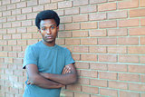 young man handsome style crossed arms brick wall urban student