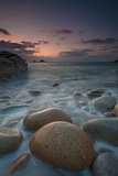 Boulders on Porth Nanven beach looking towards the Brisons at sunset Cot Valley near St Just Cornwall