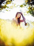 Portrait of beautiful young hippie girl with guitar. Outdoor shot