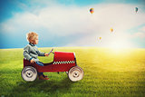 Child with car plays in a green field