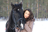 Portrait of a young black hair woman hugging a horse
