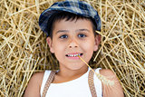 Boy with a spikelet in the teeth lies on the hay.