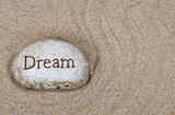 word dream on beach stone
