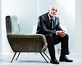 Pensive senior businessman sitting in an armchair