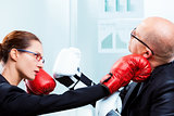 businesswoman hitting businessman's face with a punch