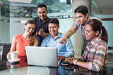 Multi-ethnic team of employees watching a funny video or presentation