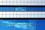 Facade of modern building. Reflection of sky and clouds in windo