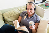 Relaxed young woman reading a book and listening to music