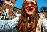 happy trendy traveller woman in Milan, Italy taking selfie