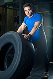 young strong athlete posing with a heavy wheel in the gym