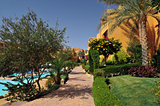 Beautiful garden at hotel resort and building in traditional arabic style. Resort architecture in Egypt