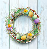 Easter wreath decoration. Branch of willow and colored eggs on blue wooden background
