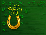 St. Patrick's day text greeting card. Golden horseshoe and green leaf clover trefoil on green board background