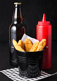 Fried chicken dippers in black bucket with beer