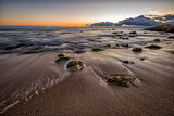 early morning at sea shore with stones on the beach