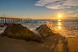 Sunrise over the sea with wave splashing on the rocks.