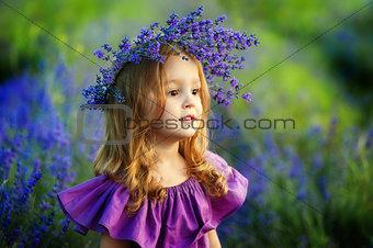 Little girl on lavender field. Portrait of a little girl in wreath of flowers