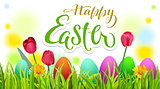 Happy easter text greeting card. Season spring green grass, colored eggs and flowers