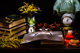 Still life of a pile of books,glasses,magnifier,vase with flowers,tea and biscuits,a lamp with a clock.Illuminated by the flashlight.