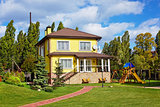 Exterior of beautiful house with green yard and children playgro