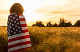 Woman Girl Teenager Wrapped in USA Flag in Field at Sunset