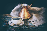 Cup of coffee and turkish coffee pot with coffee beans lying on a shabby wooden table