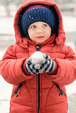 Sweet child in the snow with a snowball in his hands\