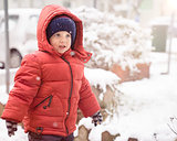 Baby boy with red jacket and hat while snows