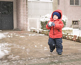 Infant runs with a snowball in his hands