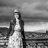 smiling tourist woman against cityscape of Barcelona, Spain