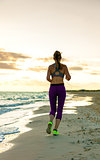 young woman in sport clothes on seashore at sunset jogging
