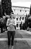young woman jogger in Rome, Italy using fitness bracelet
