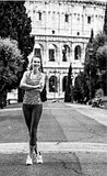 smiling young sportswoman standing in Rome, Italy