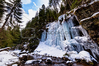 Canyon wall covered in frozen ice formations along a mountain river