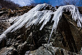 Dangerous immense icicles formed along a mountain valley and hanging above a road