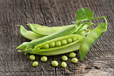 Pods of green peas on a wooden surface