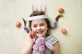 a little smiling girl in a bunny's paper ears posing with a lilac bunny toy and a brown egg as symbols of Easter