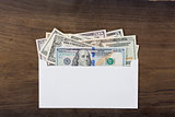 Dollar money in white envelop on wooden background.