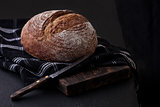 Freshly baked  bread with  kitchen towel and knife