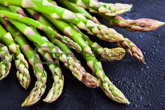 Raw fresh asparagus on dark background, close-up