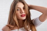 Attractive Caucasian female model in white top wearing eye make up and red lipstick
