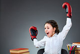 Playful cute little girl having fun in boxing gloves while leaning on grey background, selective focus